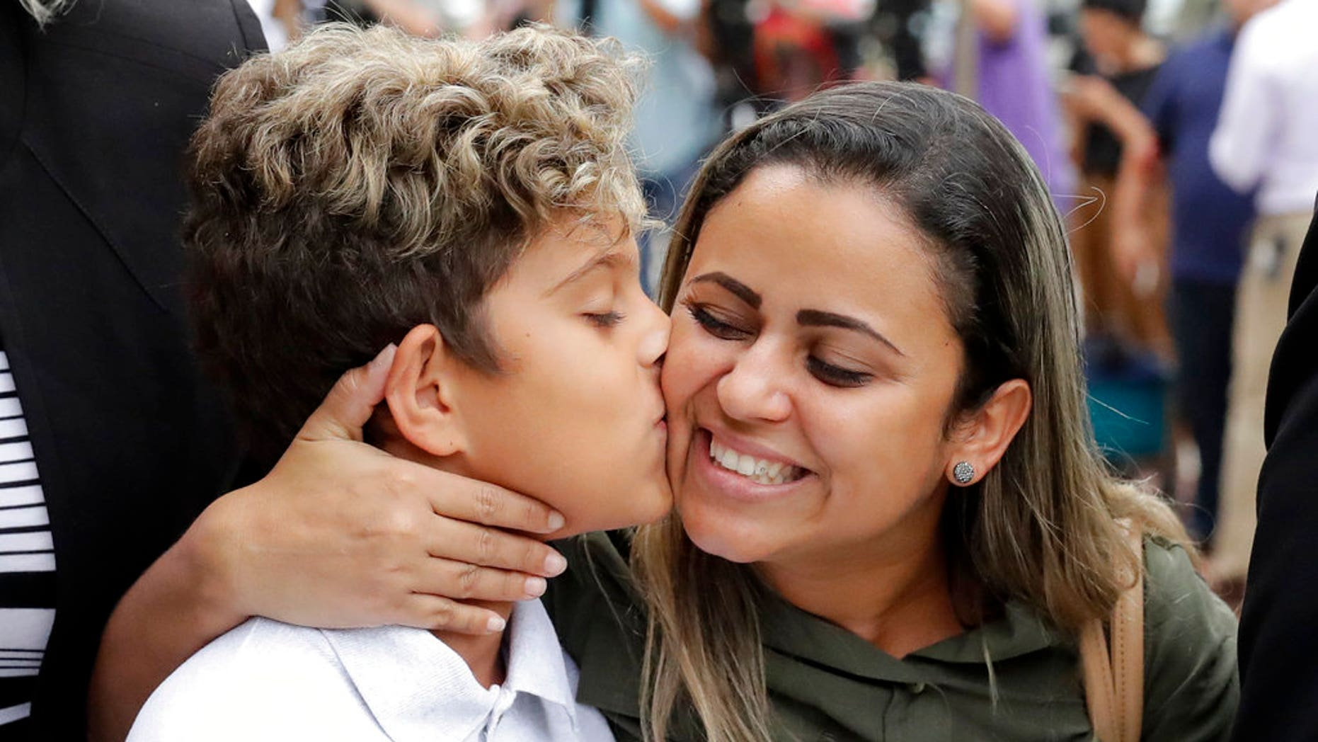 Diego Magalhaes, left, 10, kisses his mother Sirley Silveira, Paixao, an immigrant from Brazil seeking asylum with her son, after Diego was released from immigration detention, Thursday, July 5, 2018, in Chicago. (AP Photo/Charles Rex Arbogast)