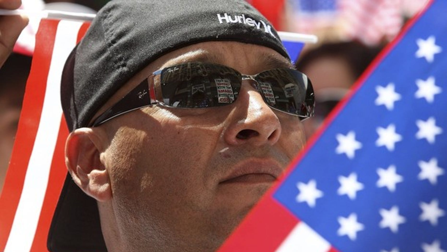 A man carrying U.S. flags joins thousands of protesters in a march up Broadway during a May Day immigration rally in Los Angeles, California, May 1, 2010. (Reuters)