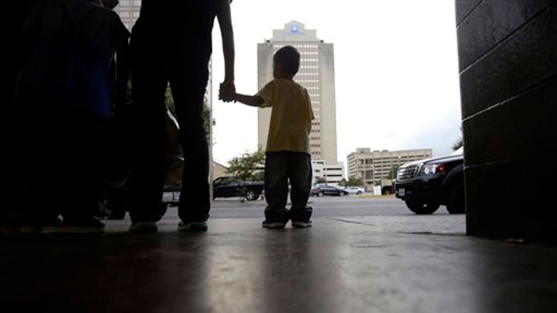 Tuesday, July 7, 2015, A young boy holds hands with his mother at a bus station after they were released from a family detention center in San Antonio, Texas.