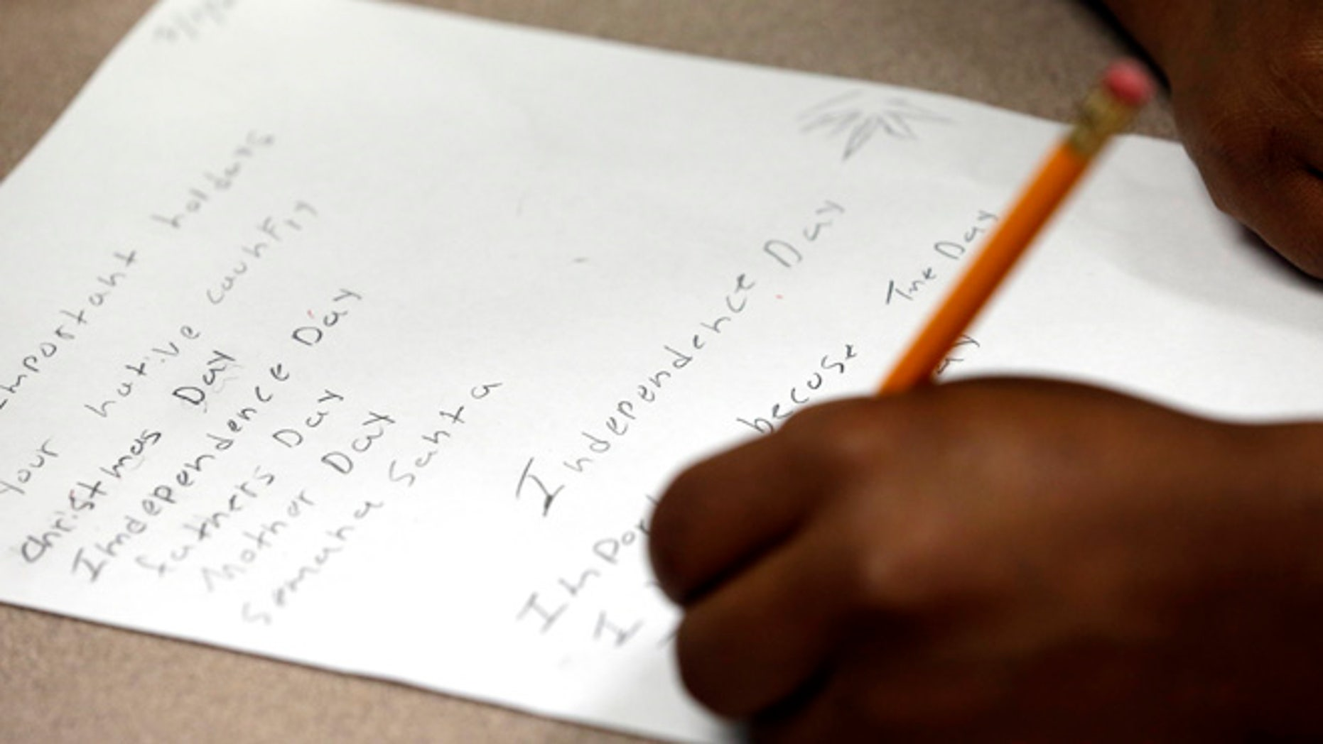 """FILE - In this July 1, 2014, file photo, a student at Liberty High School in Houston works on a holiday writing assignment. The school serves a large immigrant population, including """"unaccompanied minors."""" (AP Photo/David J. Phillip, File)"""
