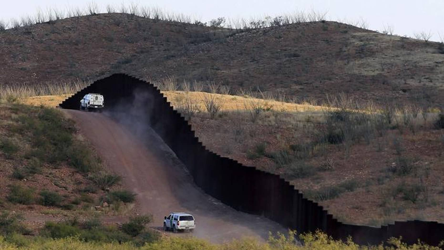 U.S. Border Patrol agents patrolling the border fence near Naco, Ariz.