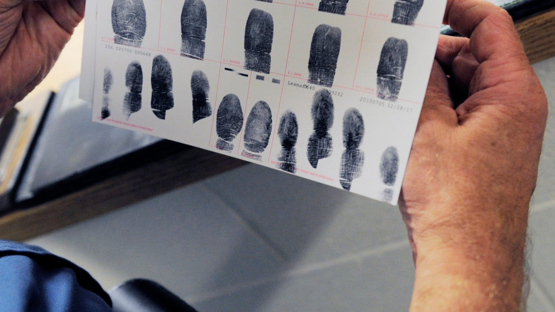 In this July 26, 2010 photo,Senior Deputy Jerry Anttila looks at a set of fingerprints for an unidentified suspect during the booking process at the Arapahoe County Justice Center in Centennial, Colo. (AP)
