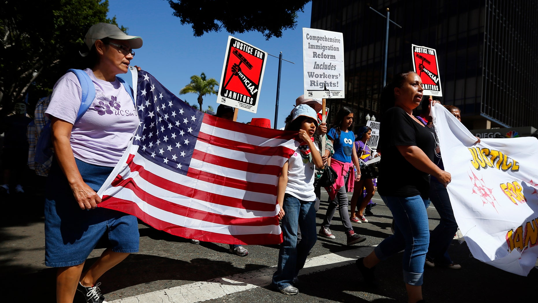 People march through the streets during a May Day demonstration in San Diego, California May 1, 2013.