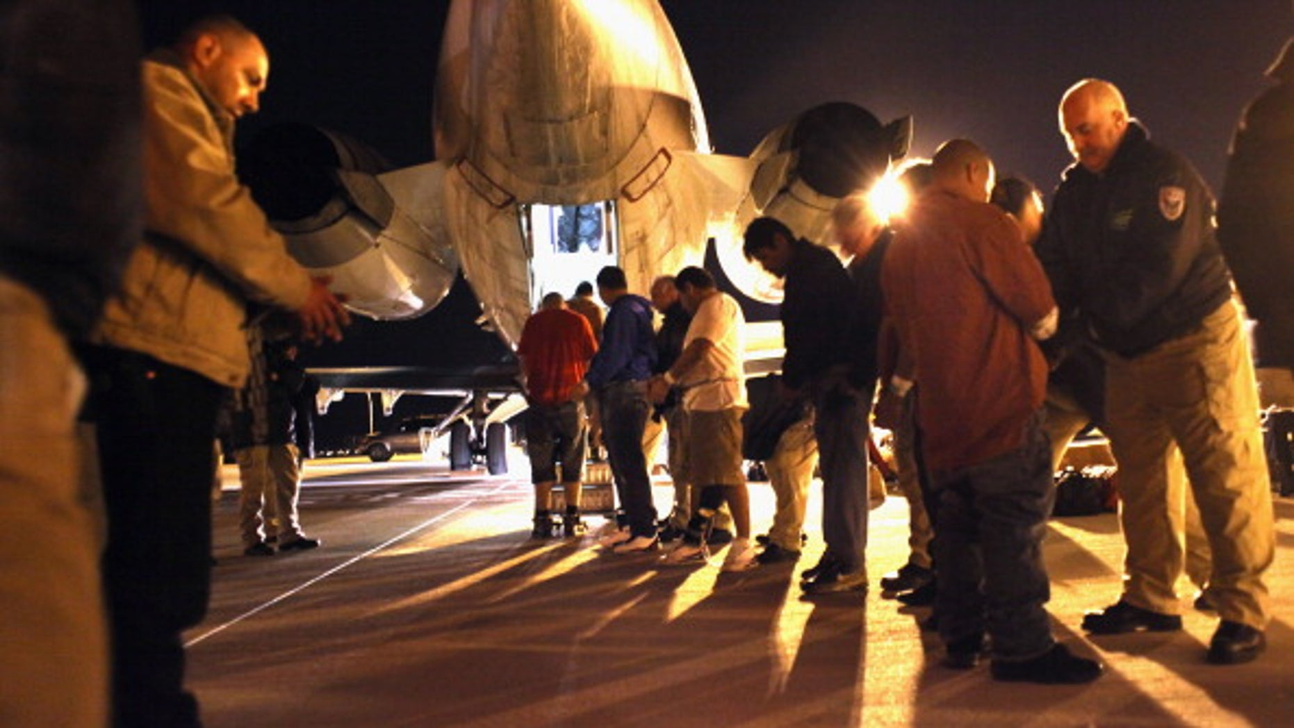 Immigration and Customs Enforcement (ICE) officers pat down undocumented  immigrants from El Salvador before boarding them onto a deportation flight on December 8, 2010 in Mesa, Arizona. (Photo by John Moore/Getty Images)