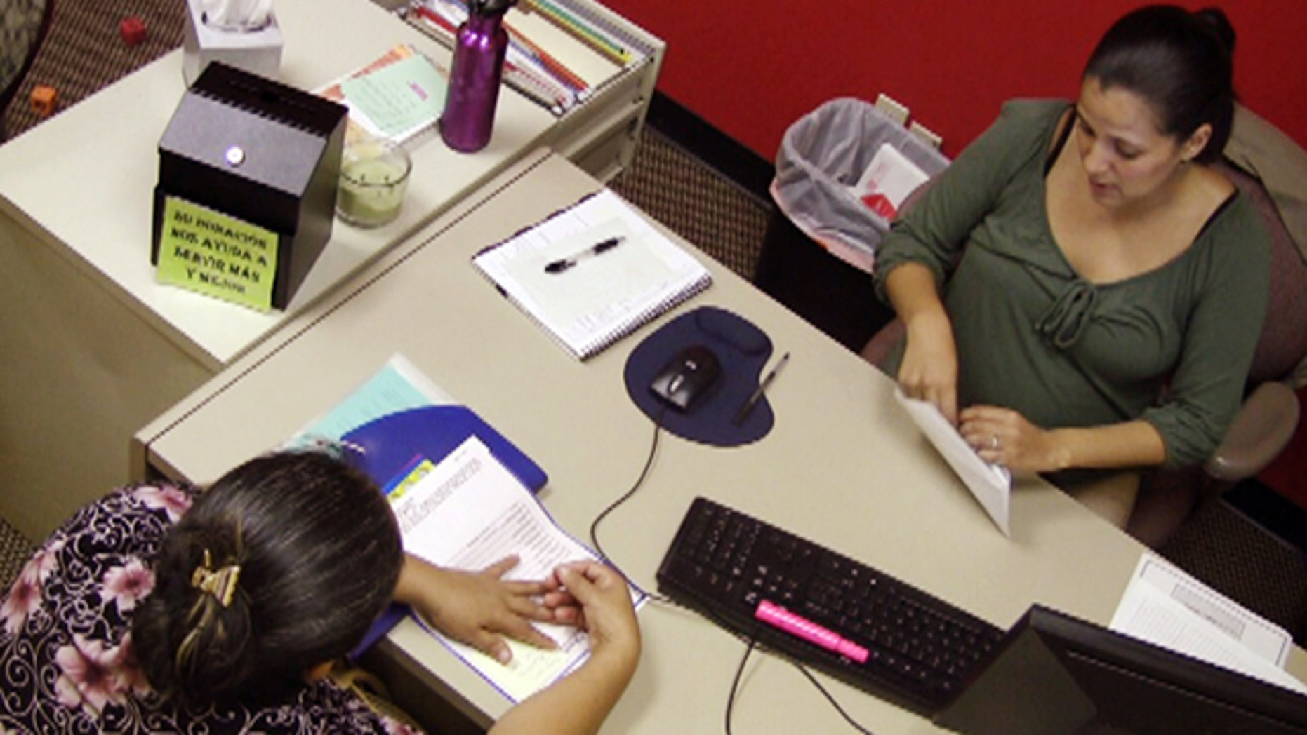 Oct. 6: In this photo taken from video, Jazmin Rivera, right, a case manager with the Hispanic Interest Coalition of Alabama, works with an unidentified immigrant in her office in Birmingham, Ala.