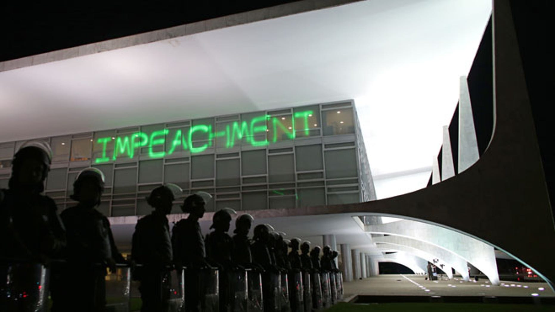 """FILE - In this March 21, 2016 file photo, soldiers stand guard outside Planalto presidential palace where protesters projected the word """"Impeachment"""" on the building, as they call for the impeachment of Brazil's President Dilma Rousseff in Brasilia, Brazil. On Thursday, the Senate will begin the final phase of Rousseff's trial for allegedly breaking fiscal rules in her management of the federal budget. Several days of deliberations, including an address by Rousseff herself, will culminate in a final vote early next week. (AP Photo/Eraldo Peres, File)"""
