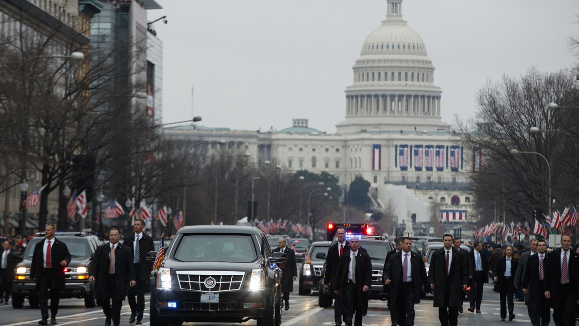 Secret Service agents escort President Donald Trump's vehicle along the inauguration day parade route after he was sworn in as the 45th President of the United States, Friday, Jan. 20, 2017, in Washington.