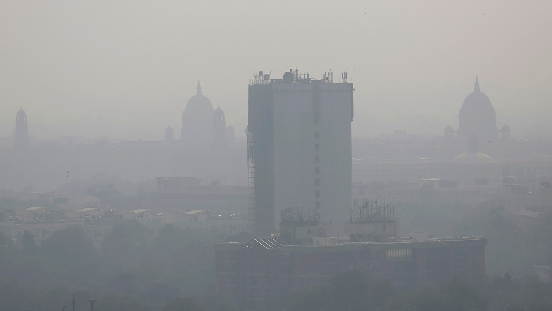 In this photo taken Friday, Oct. 28, 2016, a layer of smog envelops the city skyline before Diwali festival in New Delhi, India.