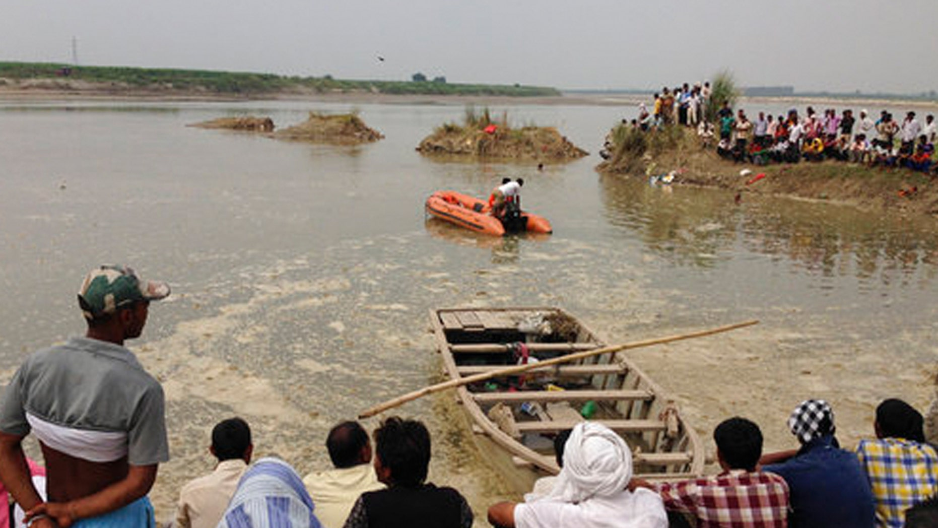 Rescuers search in the Yamuna River as villagers gather after a country boat, seen in foreground, capsized near Baghpat town in Uttar Pradesh state, India, Thursday, Sept.14, 2017. The boat crowded with construction workers capsized early Thursday and nineteen bodies have been pulled out of the river so far. (AP Photo/Altaf Qadri)