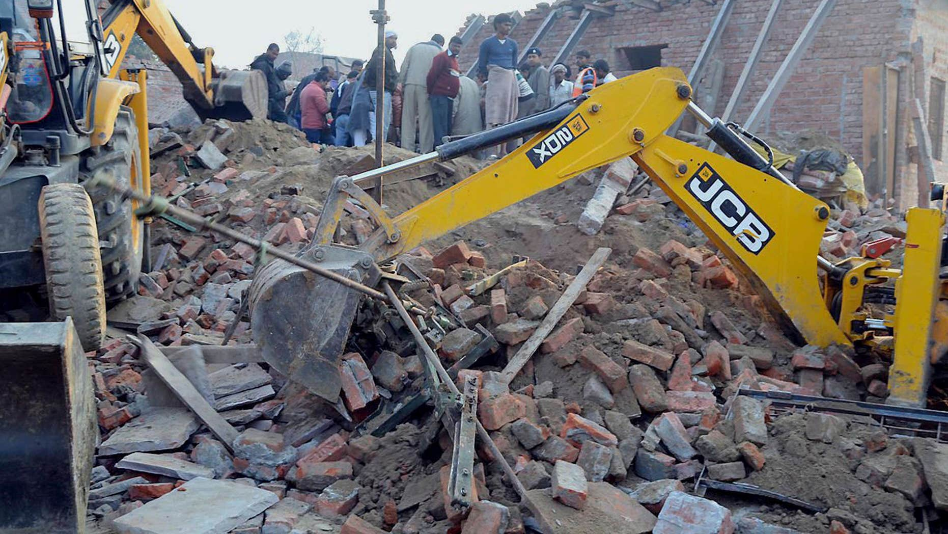 Feb. 15, 2015: Rescuers use machinery to remove the debris after a building that was under construction collapsed overnight, in the town of Mughalsarai.