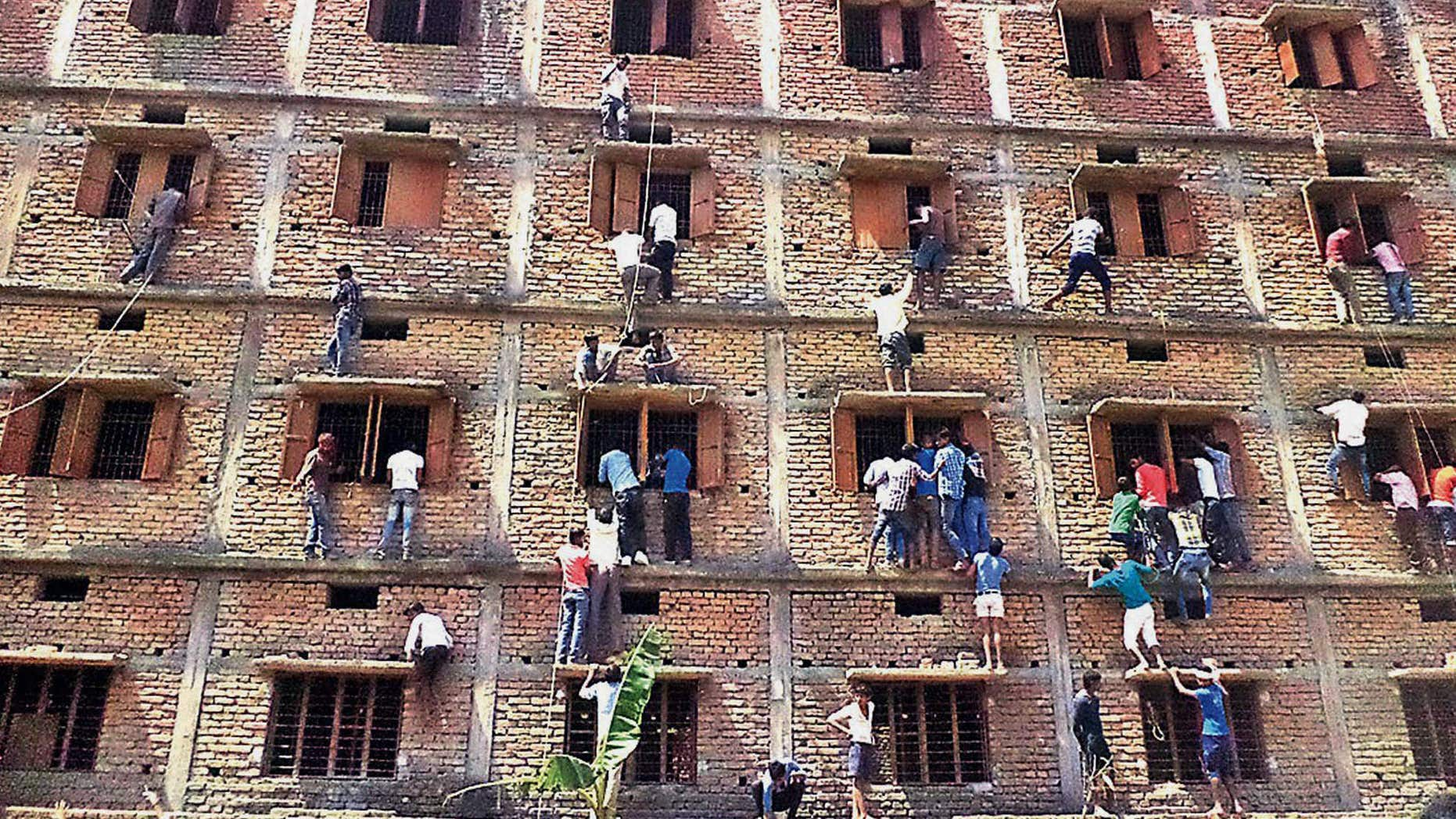 March 18, 2015: Indians climb the wall of a building to help students appearing in an examination in Hajipur, in the eastern Indian state of Bihar.