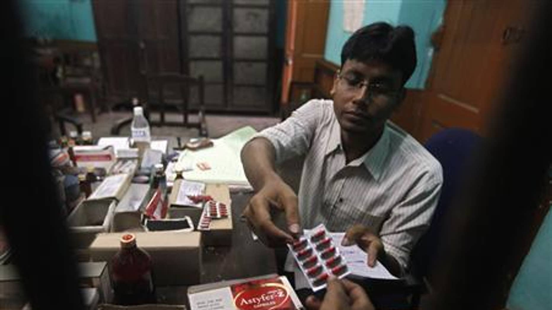 A pharmacist gives free medicine provided by the government, to a patient inside a government hospital in Kolkata July 3, 2012.