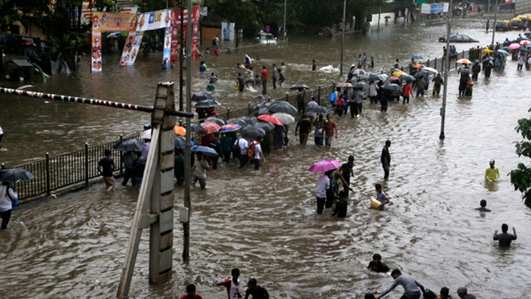 People walk through a waterlogged street after heavy rains in Mumbia, India.