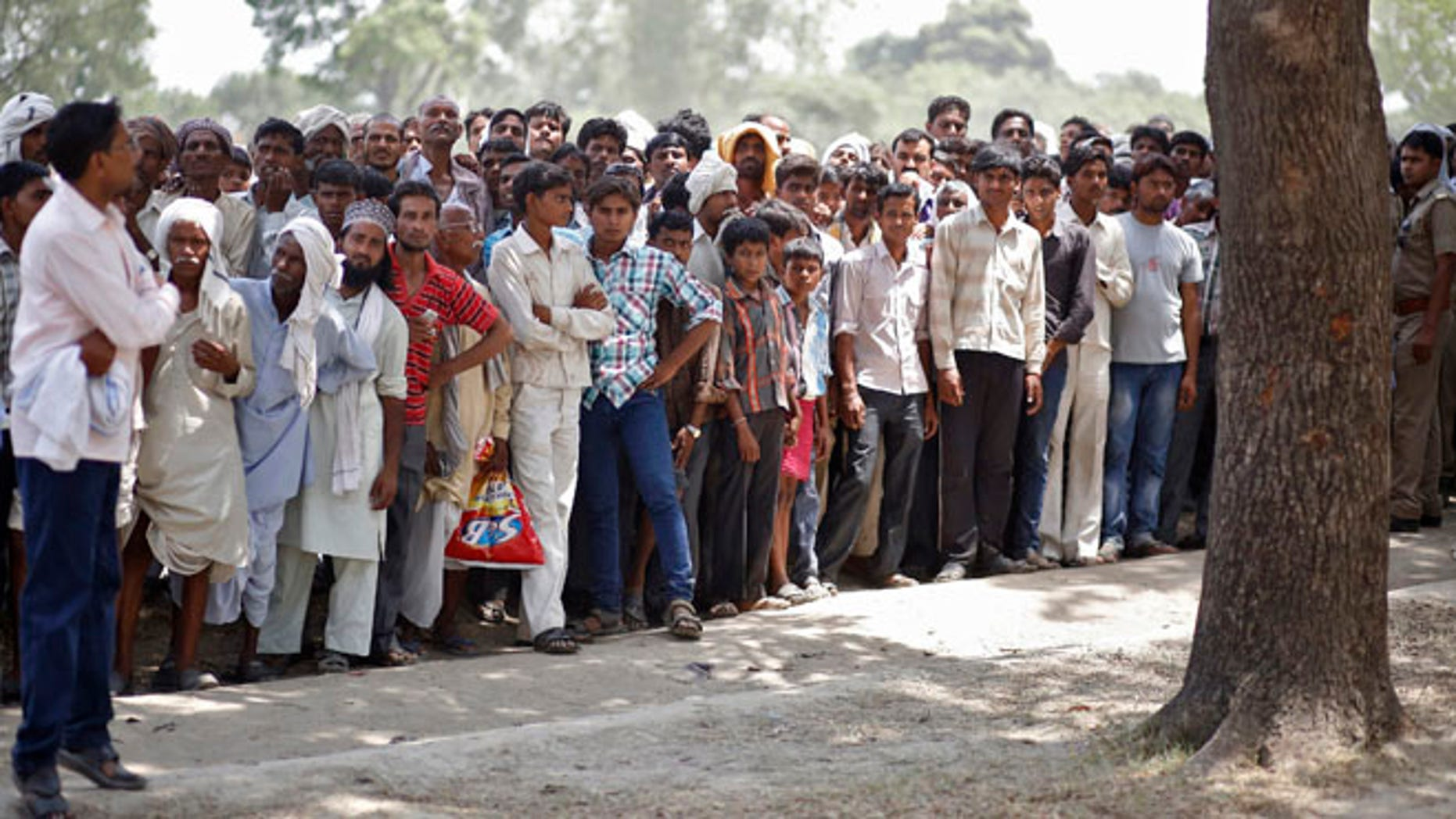 May 31, 2014: Onlookers stand at the site where two teenage girls, who were raped, were hanged from a tree in the northern Indian state of Uttar Pradesh.