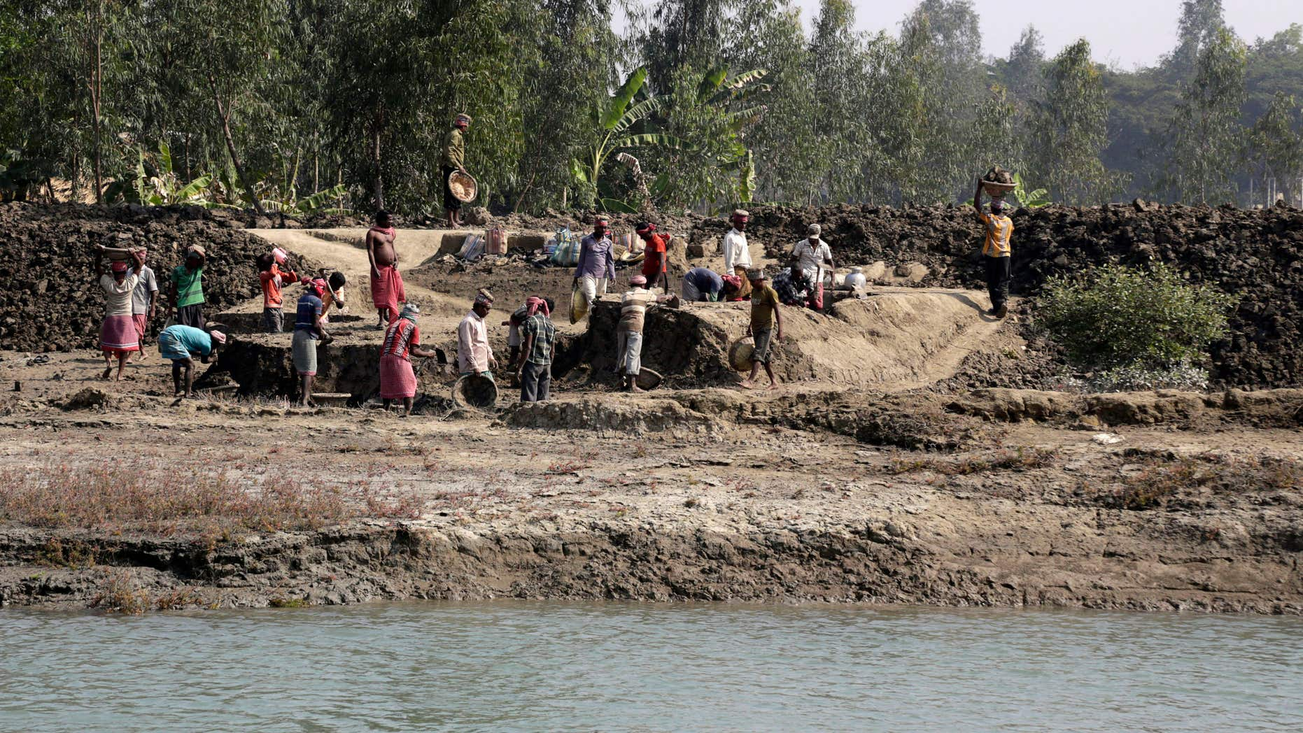 Feb. 2, 2015: Laborers work at an embankment under construction near Sonaga village in the Sundarbans, India.