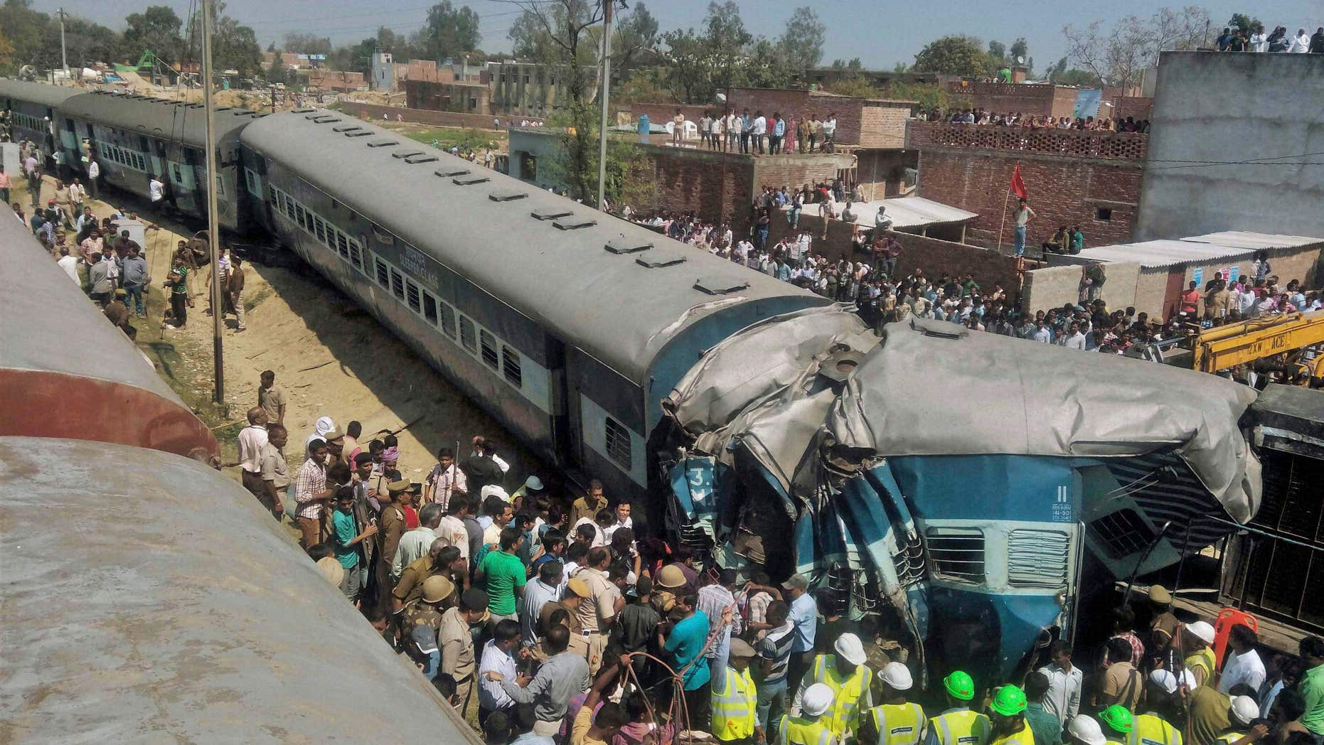 MArch 20, 2015: Indian rescue workers gather at the site of a train accident near Bachhrawan village in Uttar Pradesh state, India.