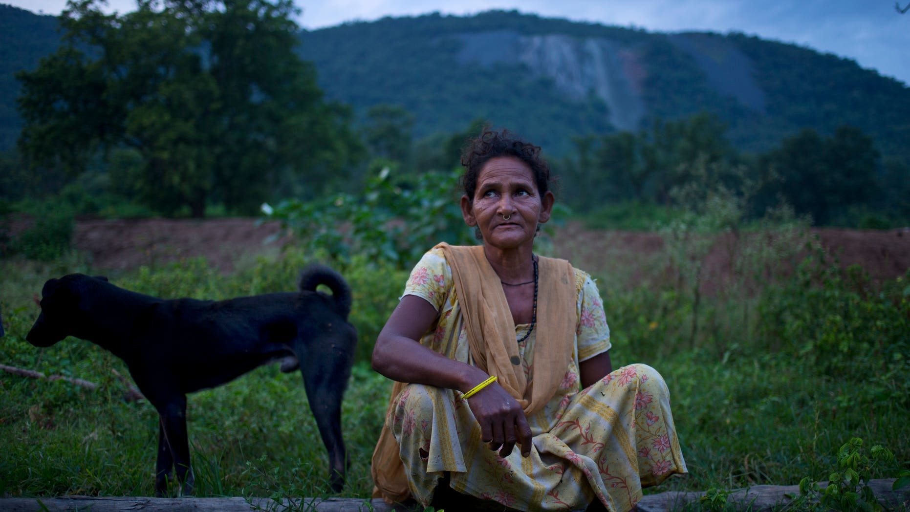 In this Sept. 11, 2014 photo, Jema Sundi sits outside her home in barren hills where asbestos waste was dumped is visible in the background in Roro, India.  (AP Photo/Saurabh Das)