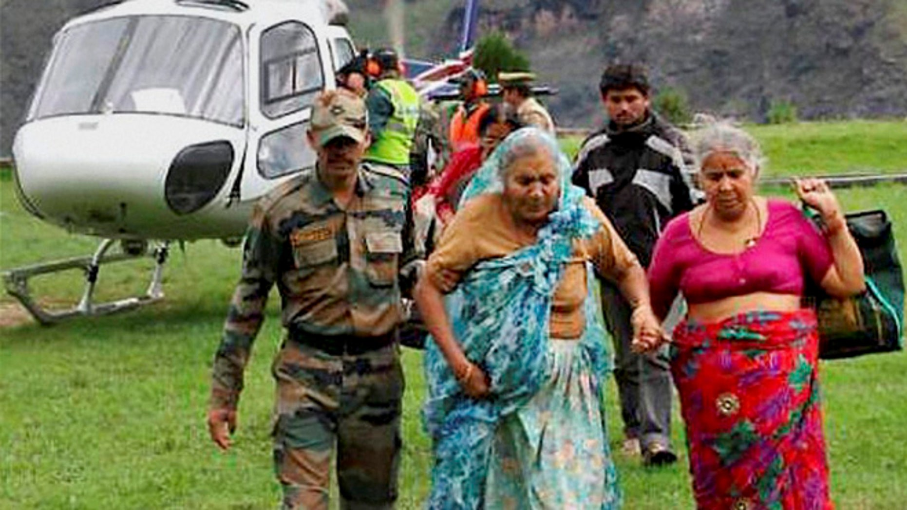 In this Wednesday June 19, 2013 photo, an Indian army soldier helps flood affected elderly pilgrims after being evacuated from upper reaches of mountains, in Chamoli, in Indian northern state of Uttrakhand. Days after floods killed more than 100 people rescuers used helicopters and climbed through mountain paths to reach nearly 4,000 people trapped by landslides in a narrow valley near a Hindu shrine in the northern Himalayas, officials said Thursday.