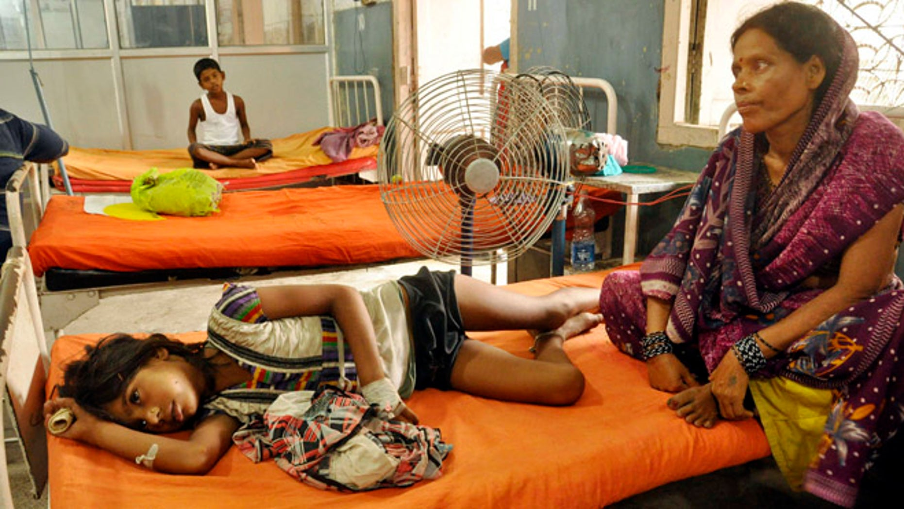 July 18, 2013: An Indian woman sits beside a child who fell sick after eating a free school lunch, at a hospital in Patna, India. Indian officials say at least 22 children have died and more than two dozen others were sickened after eating a free school lunch that was tainted with insecticide.