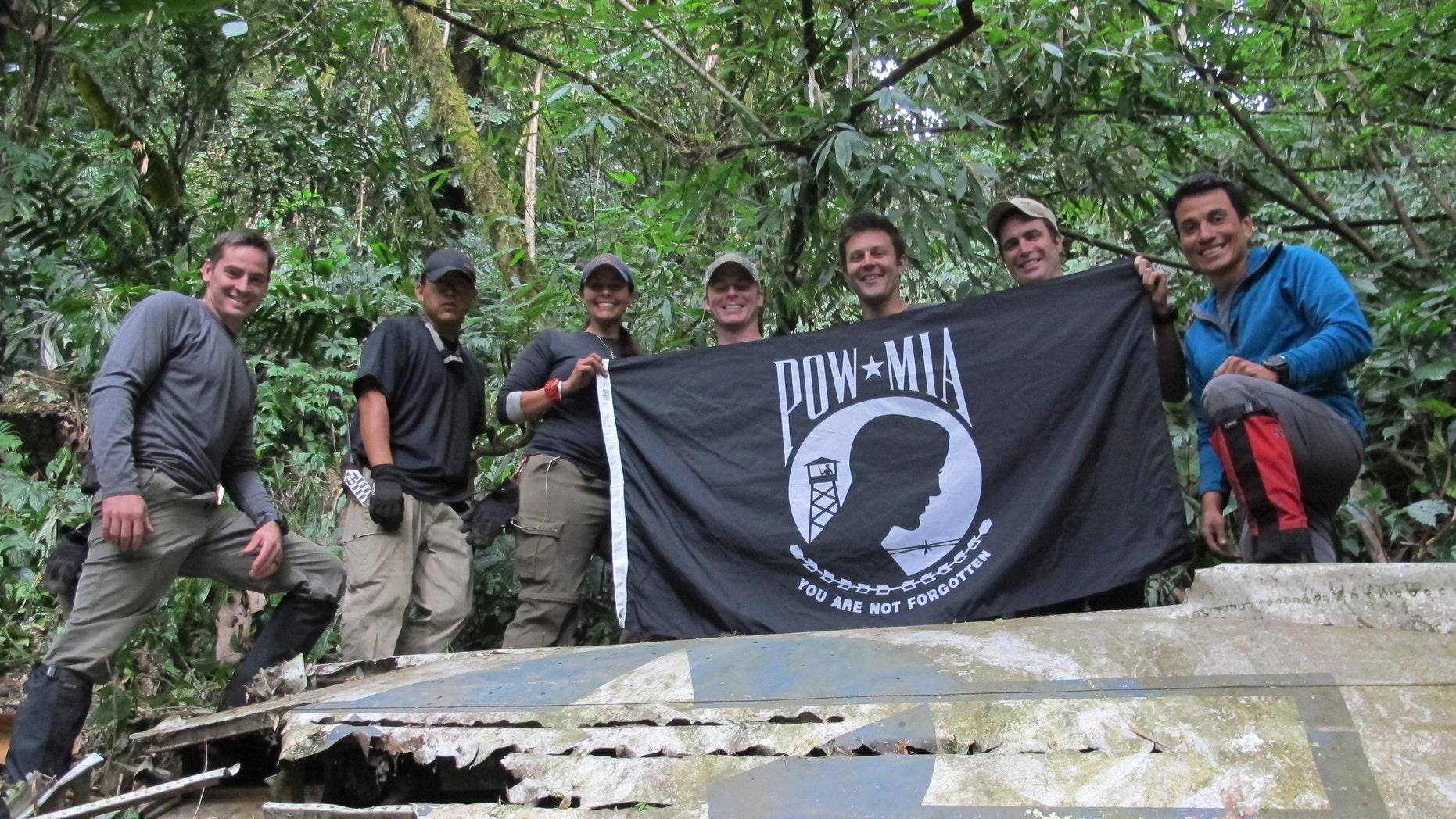 Members from Defense POW/MIA Accounting Agency (DPAA), hold the POW/MIA flag above a piece of metallic debris during a DPAA investigation mission near Bhismaknagar Village, Arunachal Pradesh, India, Dec. 02, 2016. (DoD photo by U.S. Marine Staff Sgt. Christopher Cantu)
