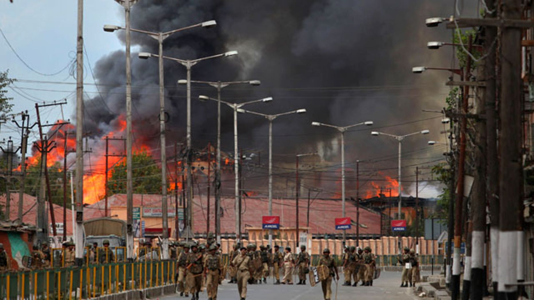 Indian forces patrol as flames rise from a government building set on fire by protesters in Srinagar, India, Saturday, Sept. 11, 2010. Police fired warning shots and tear gas to disperse hundreds of demonstrators who attacked a police post and burned government offices in Kashmir on Saturday, as tens of thousands of people took to the streets to protest Indian rule in the Himalayan region, officials said.