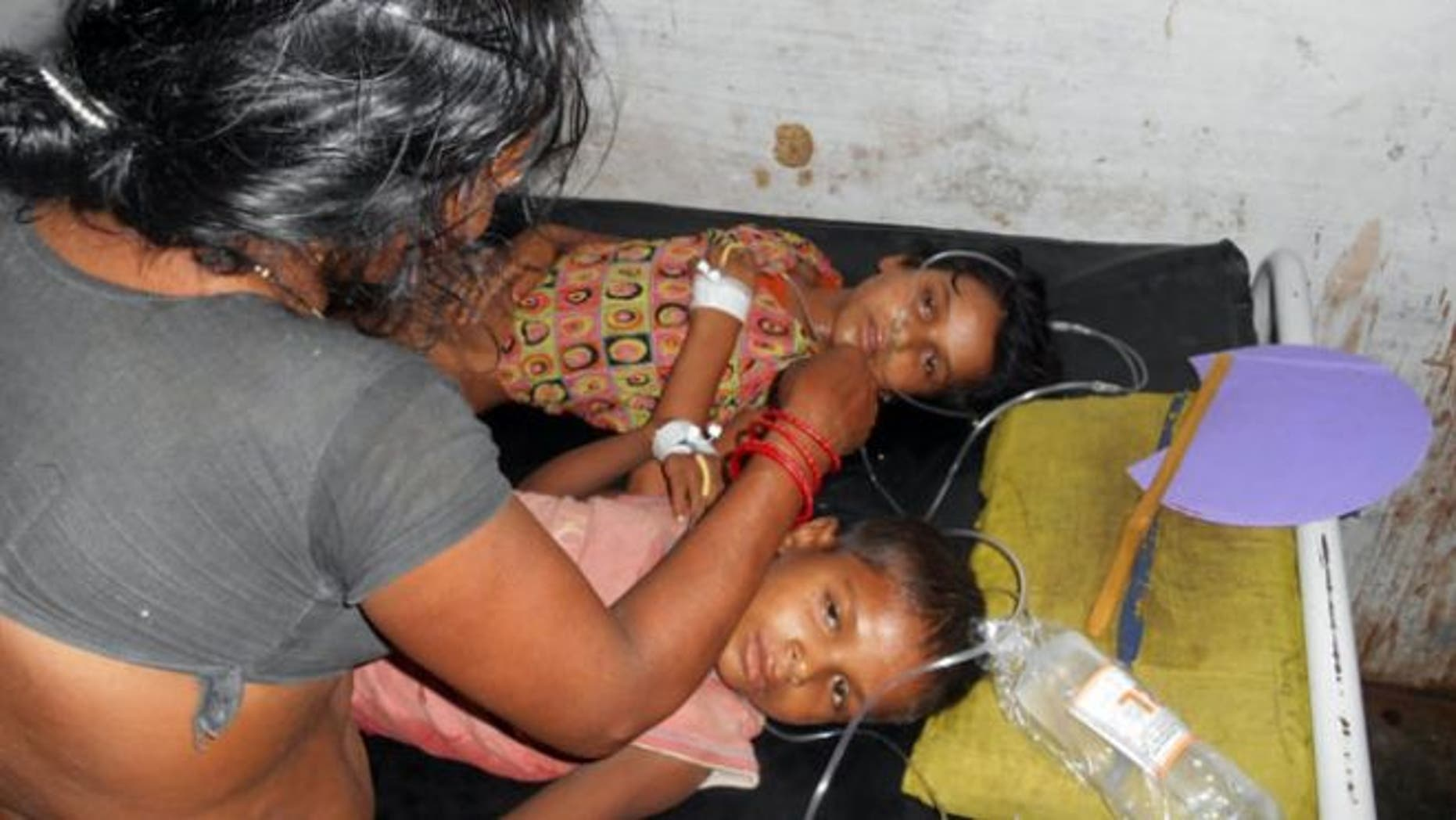July 16, 2013: Schoolchildren receive treatment at a hospital after falling ill soon after eating a free meal at a primary school in Chhapra district, in the eastern Indian state of Bihar.