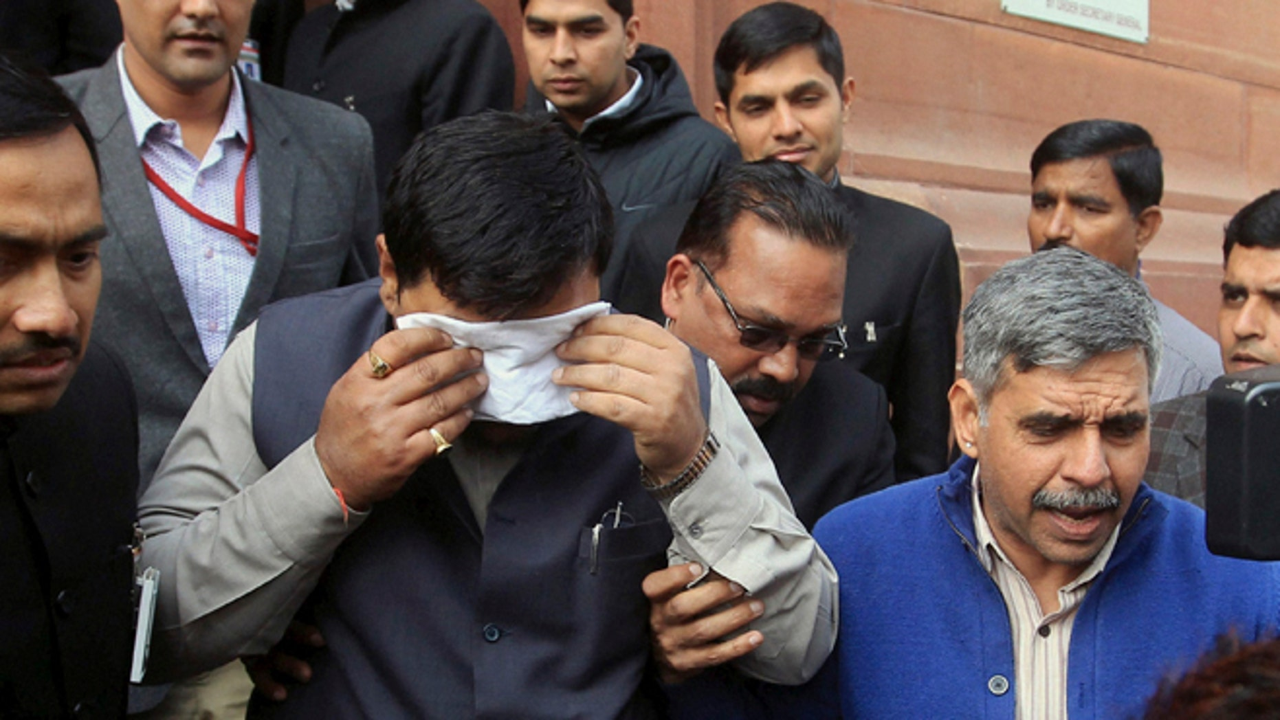 Feb. 13, 2014: An unidentified member of India's parliament covers his face with a handkerchief after being affected by pepper spray gas in New Delhi, India.