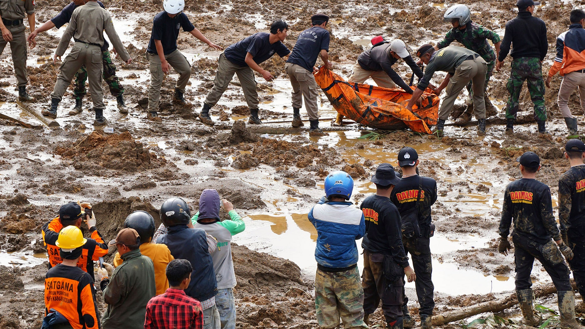 Dec. 13, 2014: Rescuers remove the body of a victim of landslides that swept away houses in Jemblung village, Central Java, Indonesia.