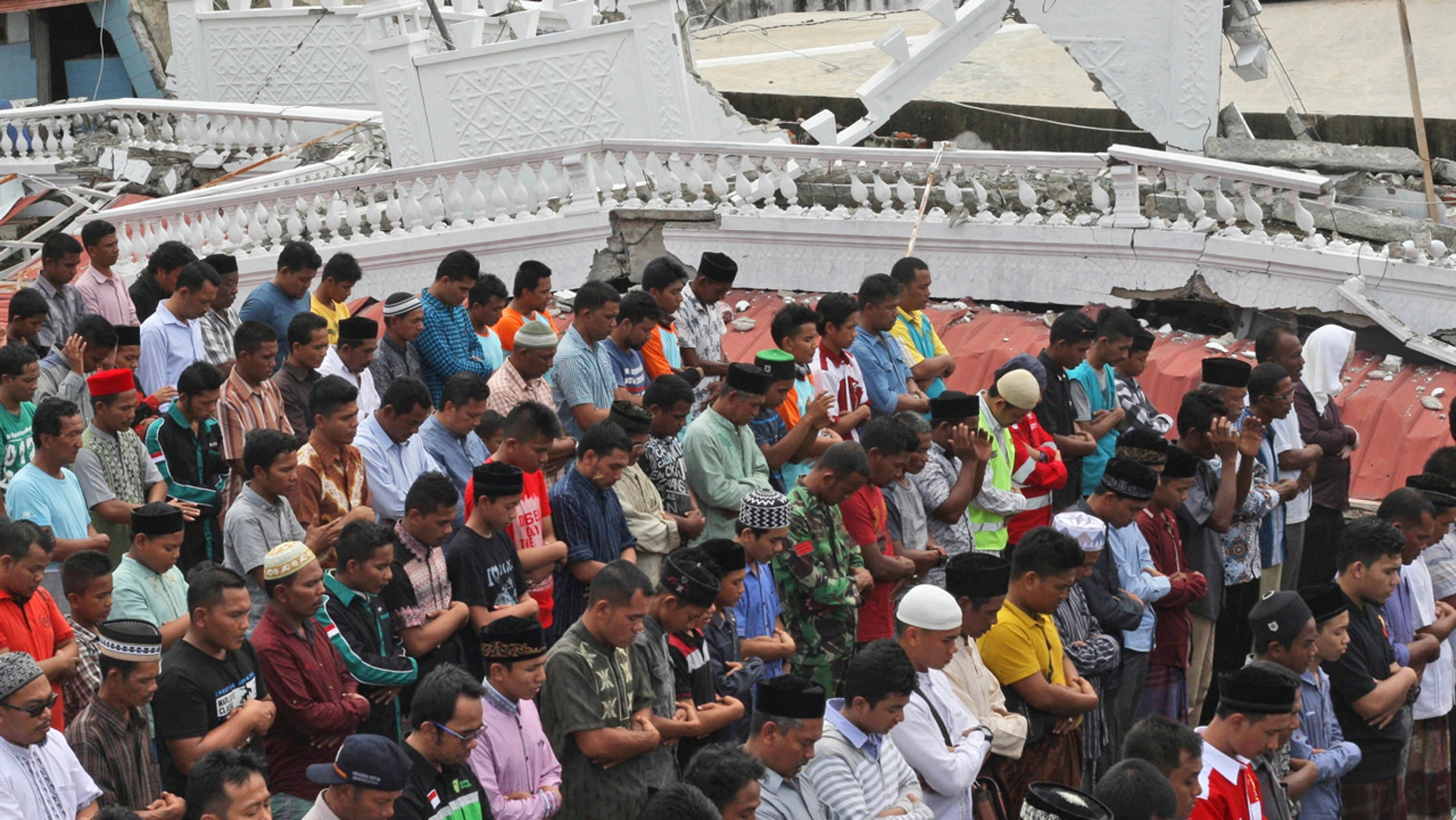 Survivors perform Friday prayer at a Jami Quba mosque which was severely damaged during Wednesday's earthquake in Tringgading, Aceh province, Indonesia, Friday, Dec. 9, 2016.