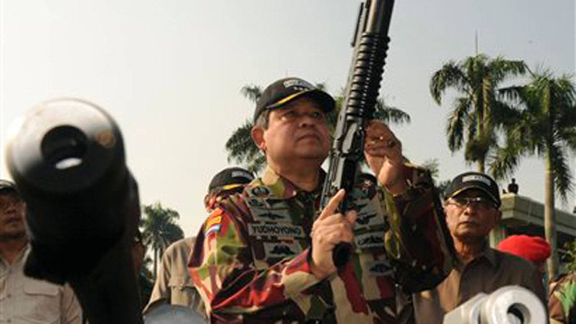 In this Aug. 20, 2009, file photo released by Indonesian Presidential Office, Indonesian President Susilo Bambang Yudhoyono, center, inspects an assault rifle during his visit to Special Forces Commandos (KOPASSUS) headquarters in Jakarta, Indonesia.