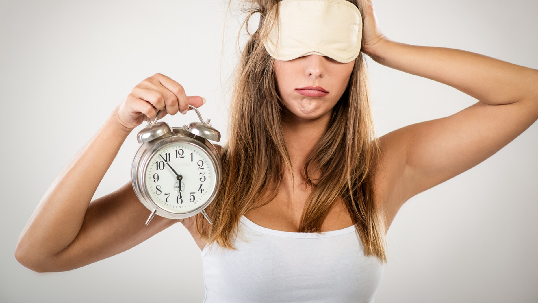 Beautiful young woman with sleeping mask holding alarm clock. She is tired and lazy in morning.
