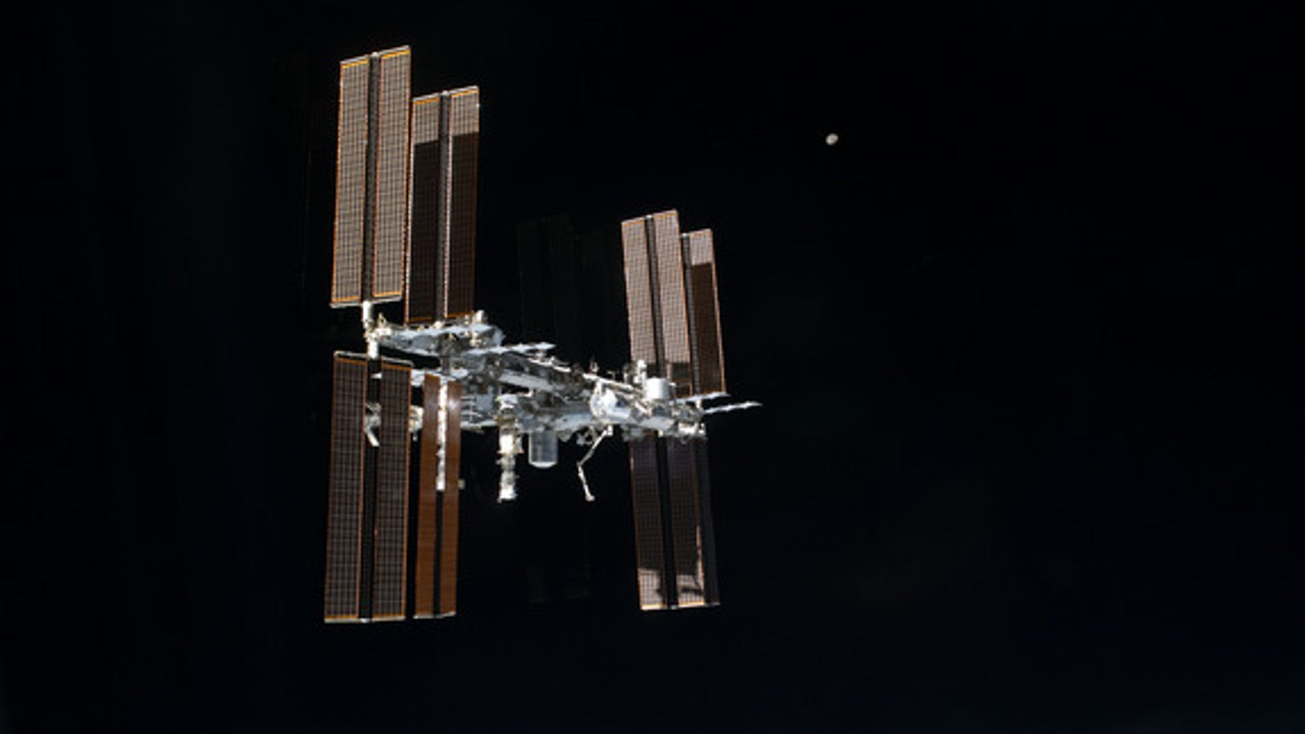 This picture of the International Space Station and the moon was photographed from the space shuttle Atlantis just after the two spacecraft undocked on July 19, 2011, during NASA's final shuttle mission STS-135.