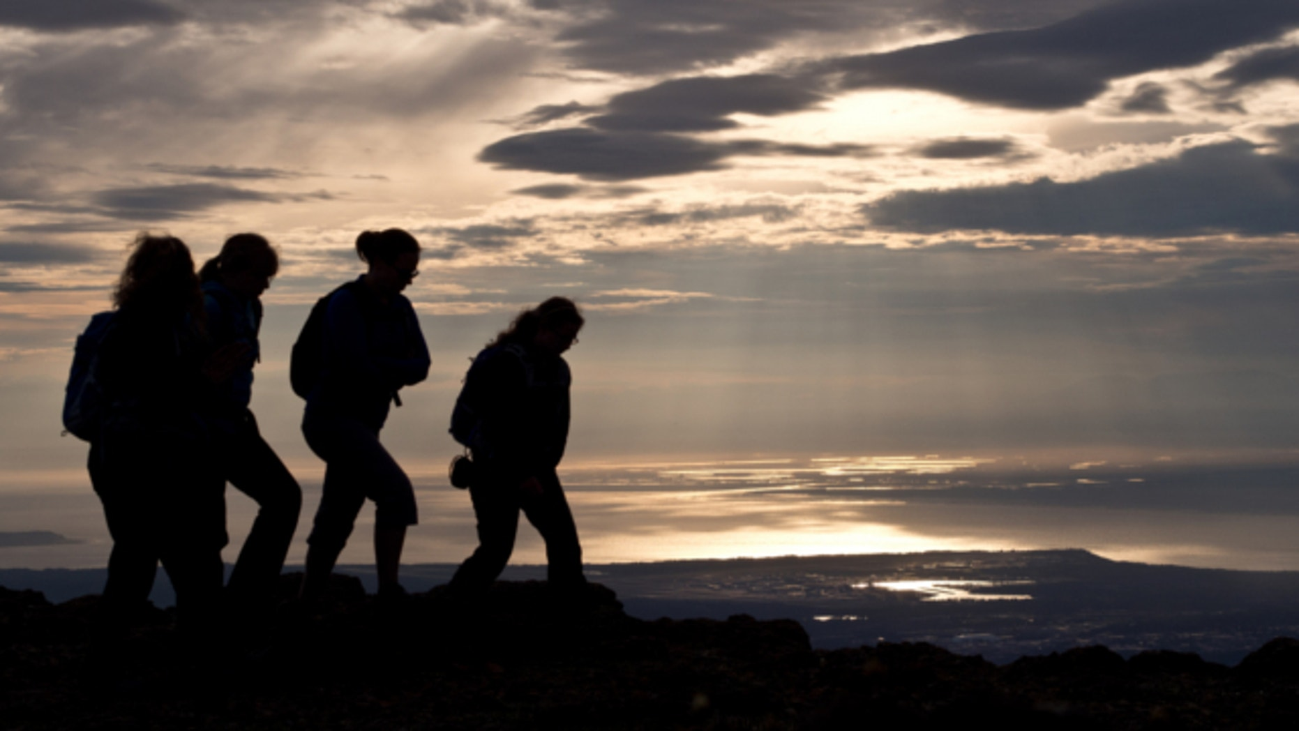 June 20, 2013: Hikers take in the view of Anchorage, Alaska, on the evening of summer solstice.