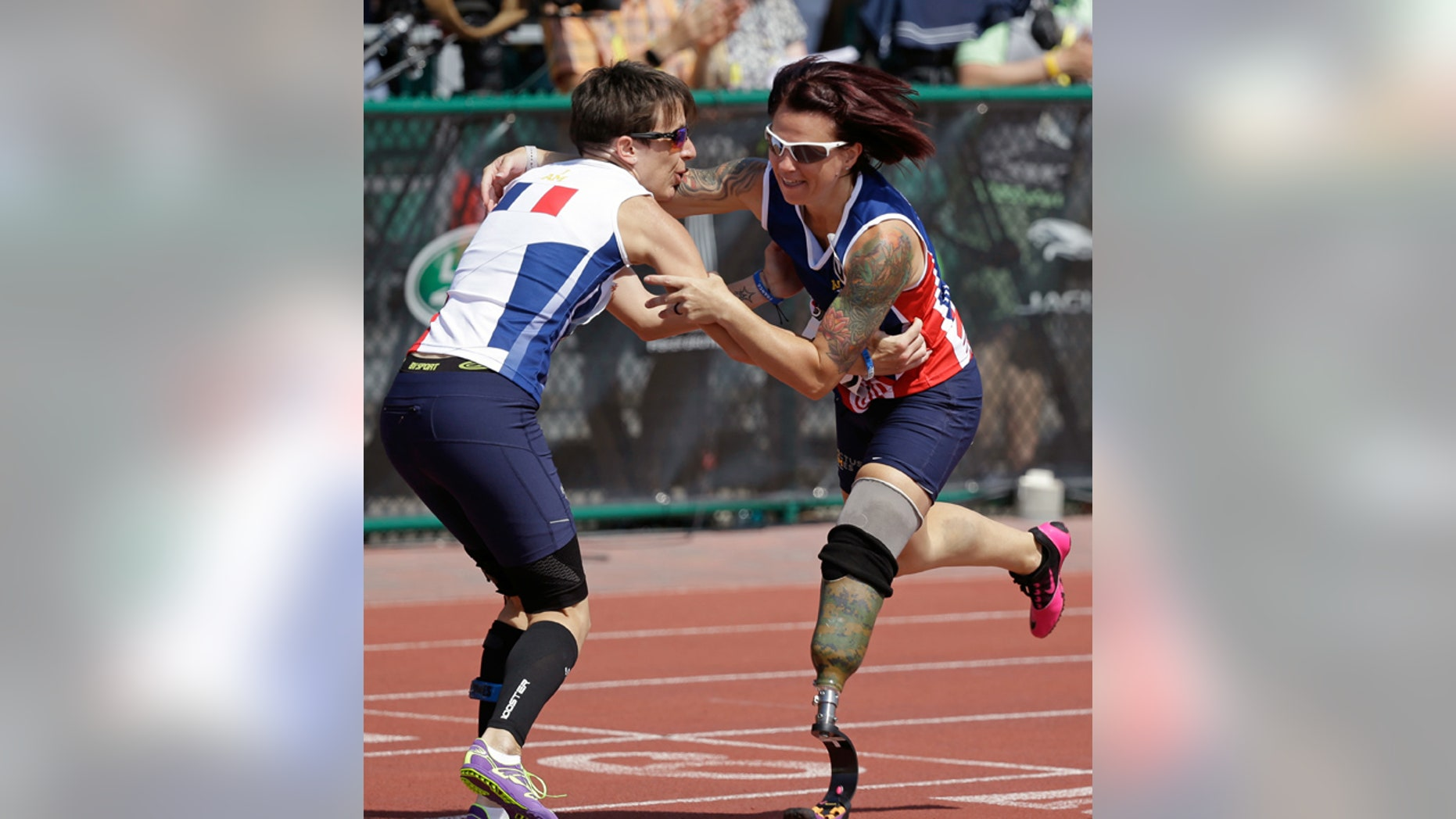 May 10, 2016: Marion Blot, left, of France, the winner of the women's 200 meter IT1 race, catches Sarah Rudder of the United States as she stumbles across the finish line at the Invictus Games in Kissimmee, Fla.