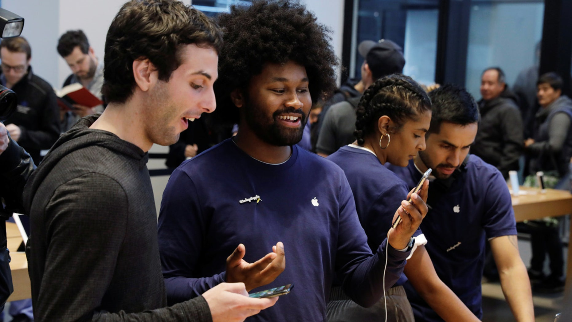 An Apple sales associate speaks with a customer waiting to purchase a new iPhone X in New York, November 3, 2017.