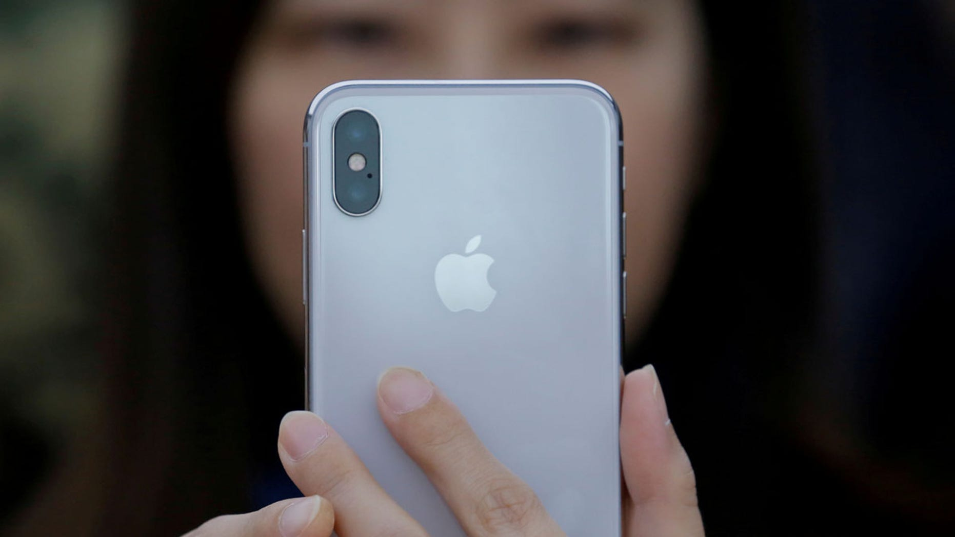 A attendee uses a new iPhone X during a presentation for the media in Beijing, China, Oct. 31, 2017.