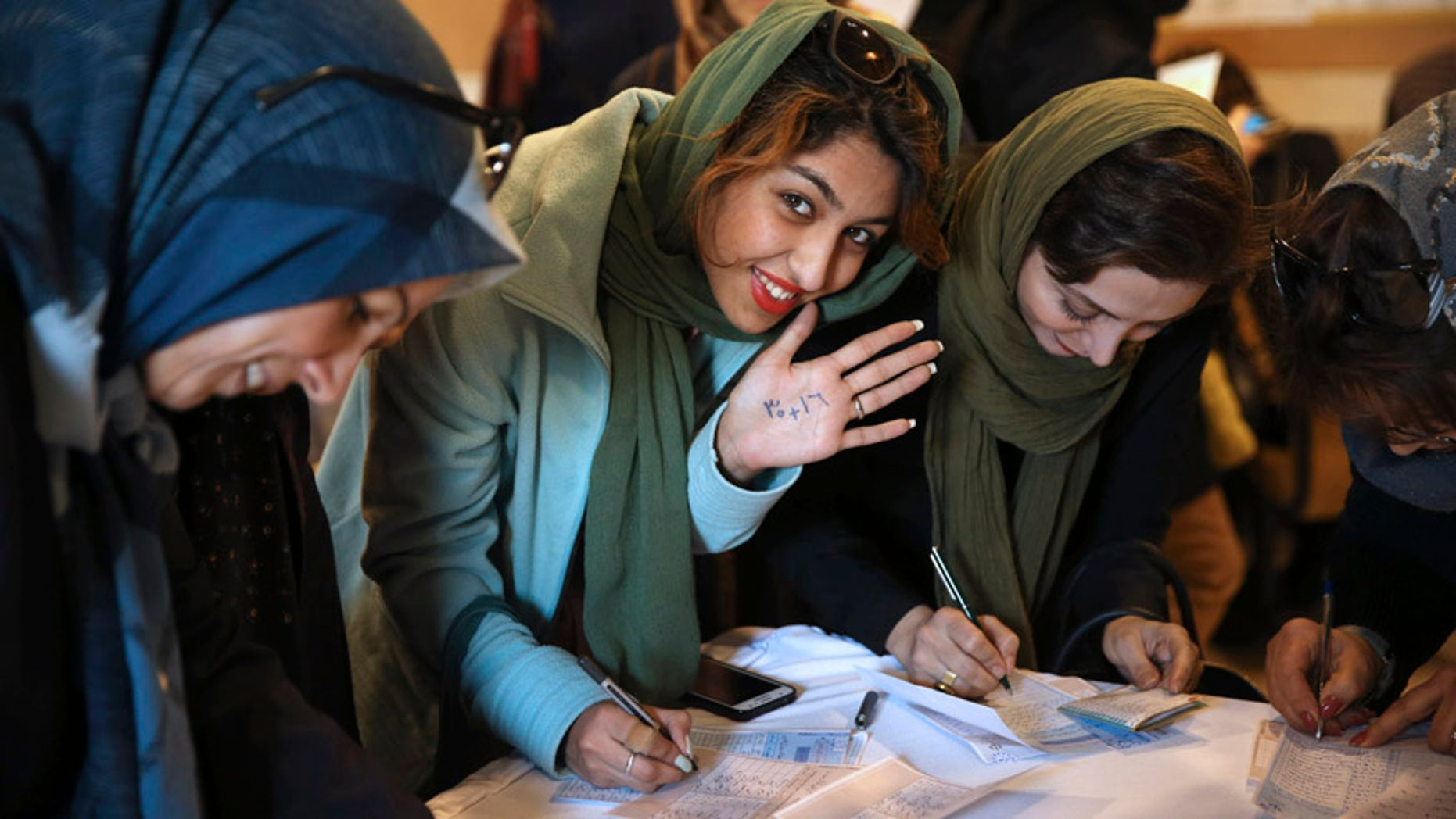 Feb. 26, 2016: An Iranian voter shows her hand with numbers 30+16, a reformists slogan urging people to vote all reformists and moderate candidates in Tehran for both parliament and Assembly of Experts during the elections, as she fills out her ballot in a polling station in Tehran, Iran.