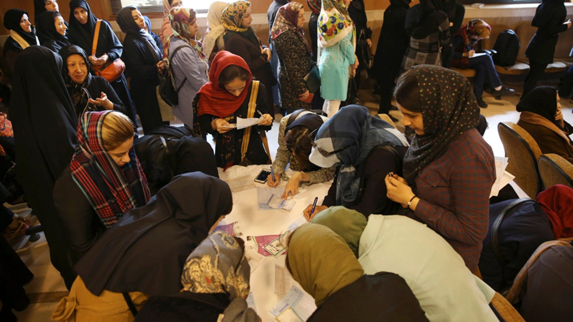 Feb. 26, 2016: A group of Iranian voters fill out their ballots as the others queue for getting ballot papers during the parliamentary and Experts Assembly elections in a polling station in central Tehran, Iran.