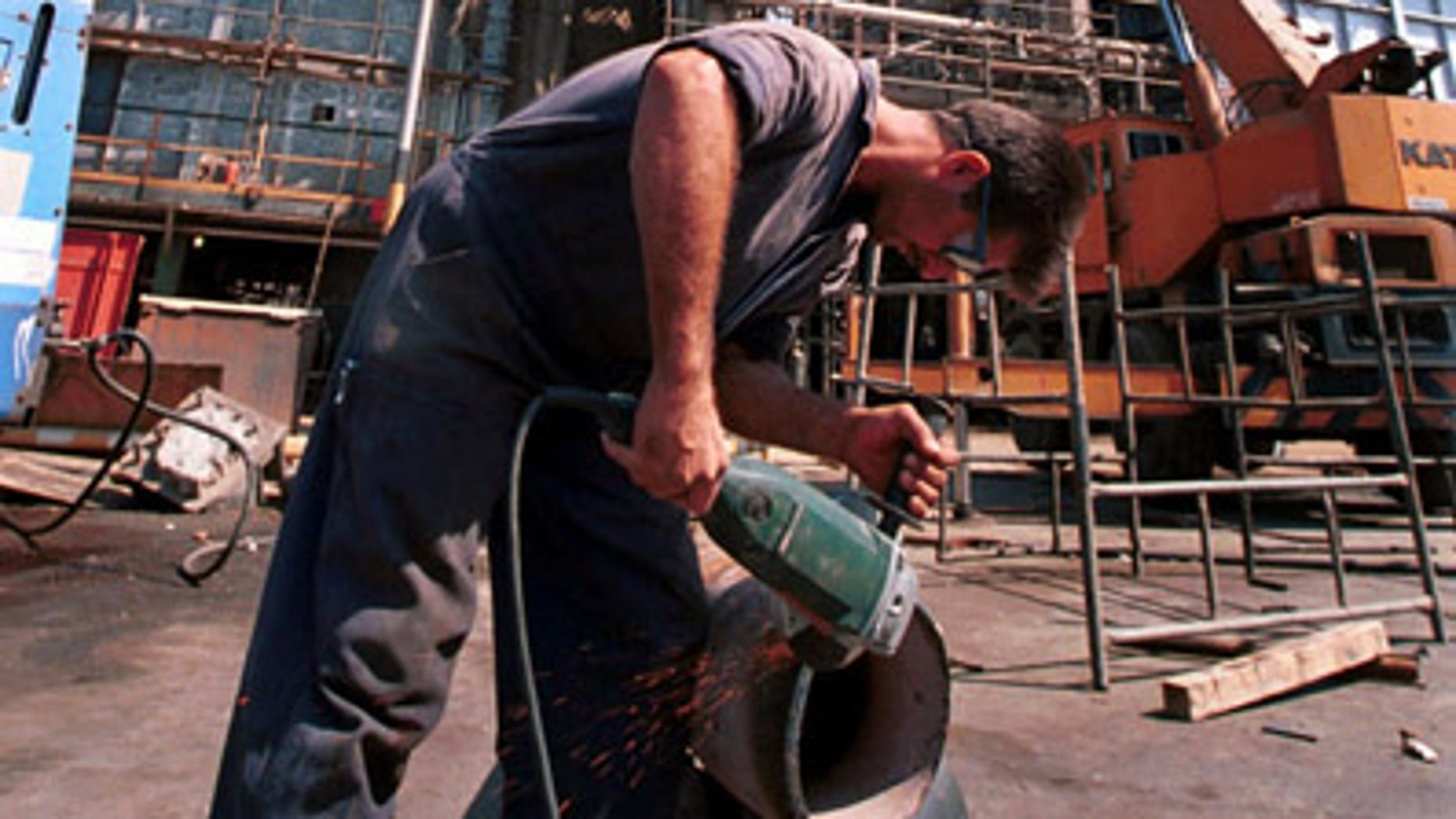 In this Sept. 27, 2000 file photo, an Iranian oil worker repairs a pipe at an oil refinery in Tehran. Iran has halted oil shipments to Britain and France, the Oil Ministry said Sunday, in an apparent pre-emptive blow against the European Union after the bloc imposed sanctions on Iran's crucial fuel exports.