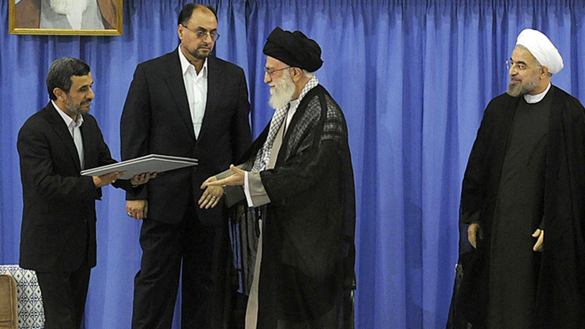 Aug. 3, 2013: In this picture released by the official website of the Iranian supreme leader's office, outgoing President Mahmoud Ahmadinejad, left, delivers the official seal of approval of Supreme Leader Ayatollah Ali Khamenei, center, to give to President-elect Hasan Rouhani, right, in an official endorsement ceremony, in Tehran, Iran.