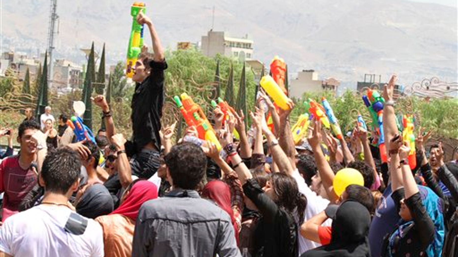 In this picture taken on Friday, July 29, Iranian youths celebrate with their water guns, during their water fights at the Water and Fire Park in northern Tehran, Iran. Iran is trying to put down a new wave of civil disobedience - flash mobs of young people who break into boisterous fights with water guns in public parks.