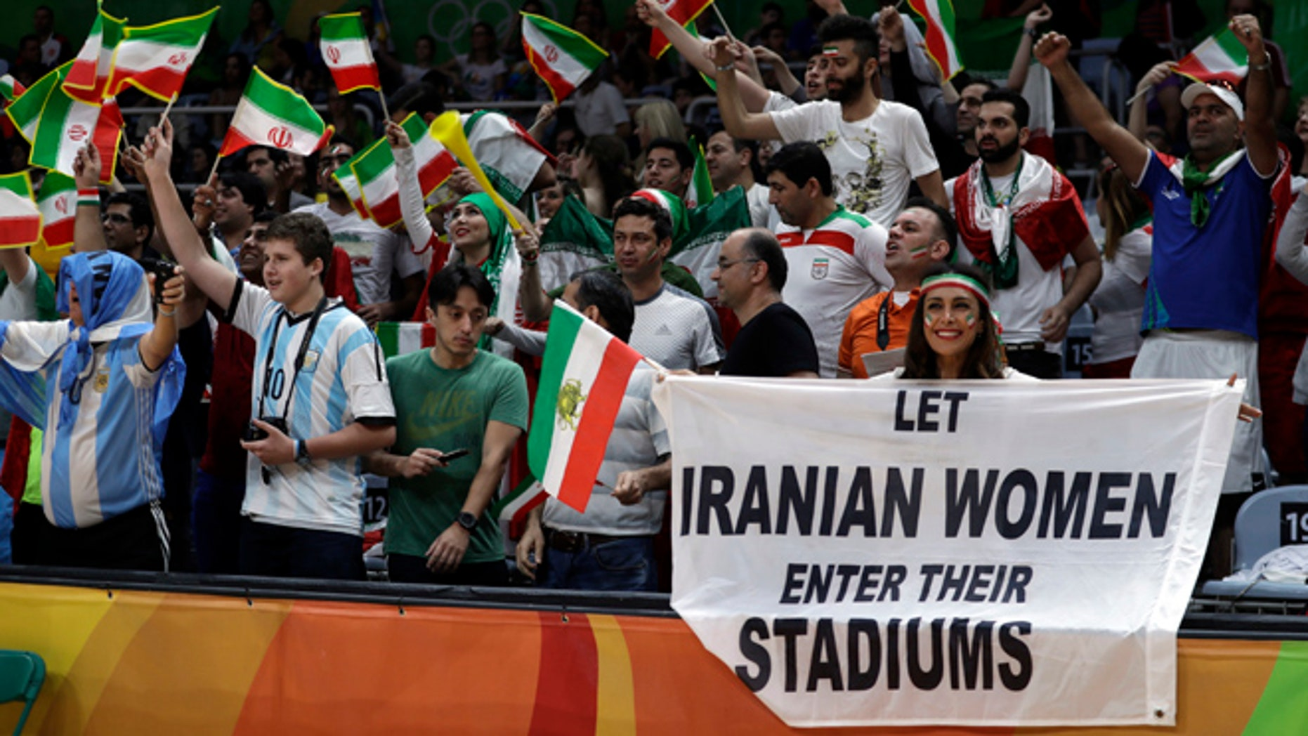 Fans cheer and wave the flag of Iran as Darya Safai, right, holds a large sign protesting the fact that women have not been allowed to attend volleyball matches in Iran during a men's preliminary volleyball match between Egypt and Iran at the 2016 Summer Olympics in Rio de Janeiro, Brazil, Saturday, Aug. 13, 2016.