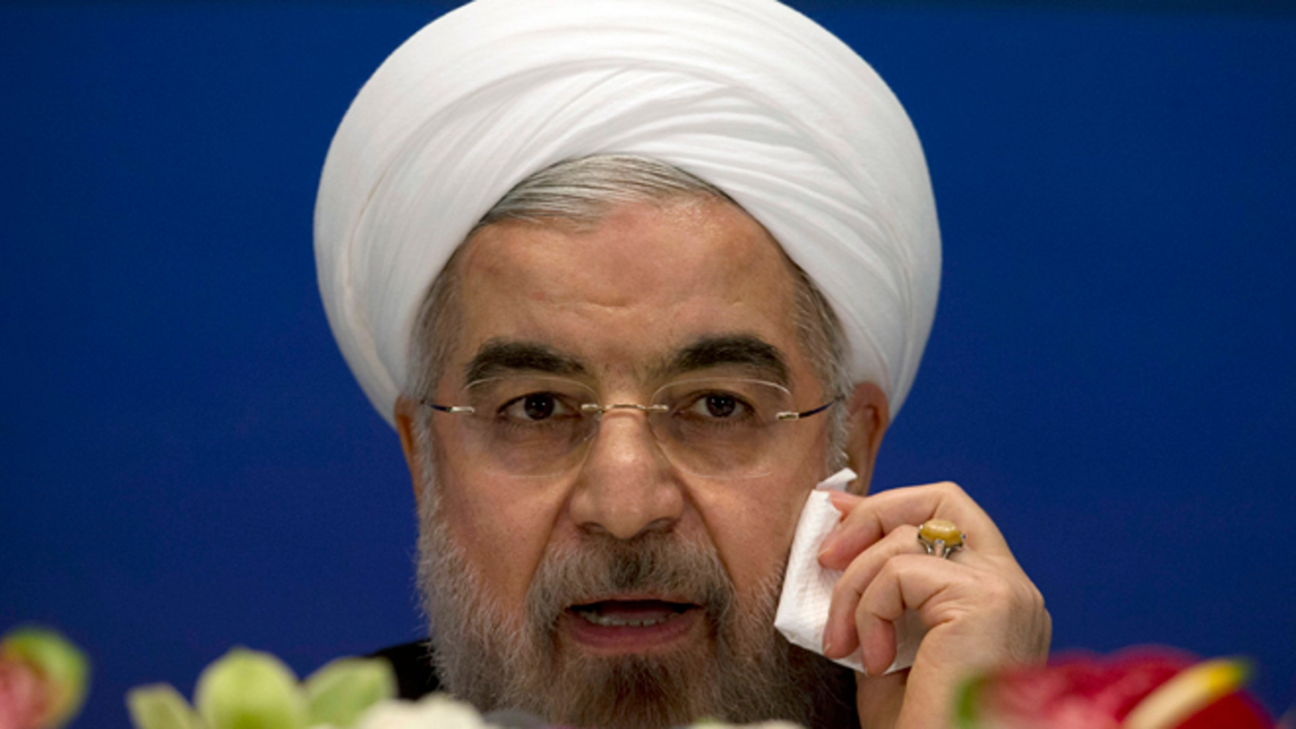 May 22, 2013: Iranian President Hassan Rouhani wipes his cheek as he speaks during a press conference at a hotel in Shanghai, China.