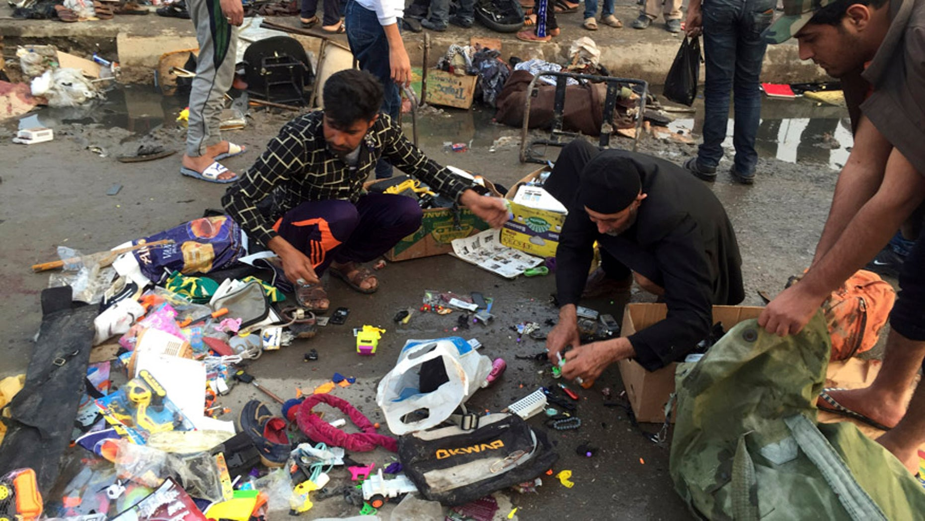 Feb. 28, 2016: Street vendors collect their belongings after deadly bombing attacks in Sadr City, Baghdad, Iraq.