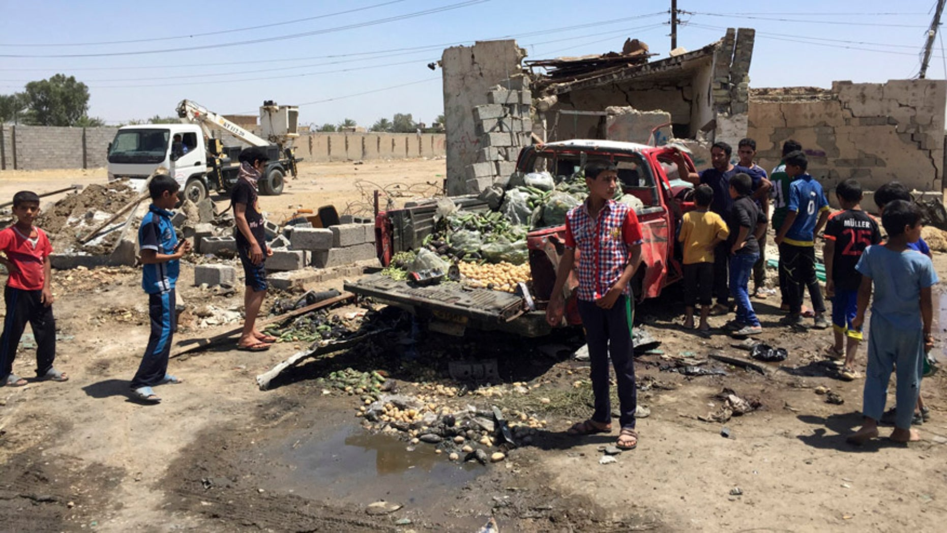 April 30, 2016: Civilians inspect the scene of car bombing at an open-air market selling fruit, vegetables and meat in Baghdad's southeast suburb of Nahrawan, Iraq.