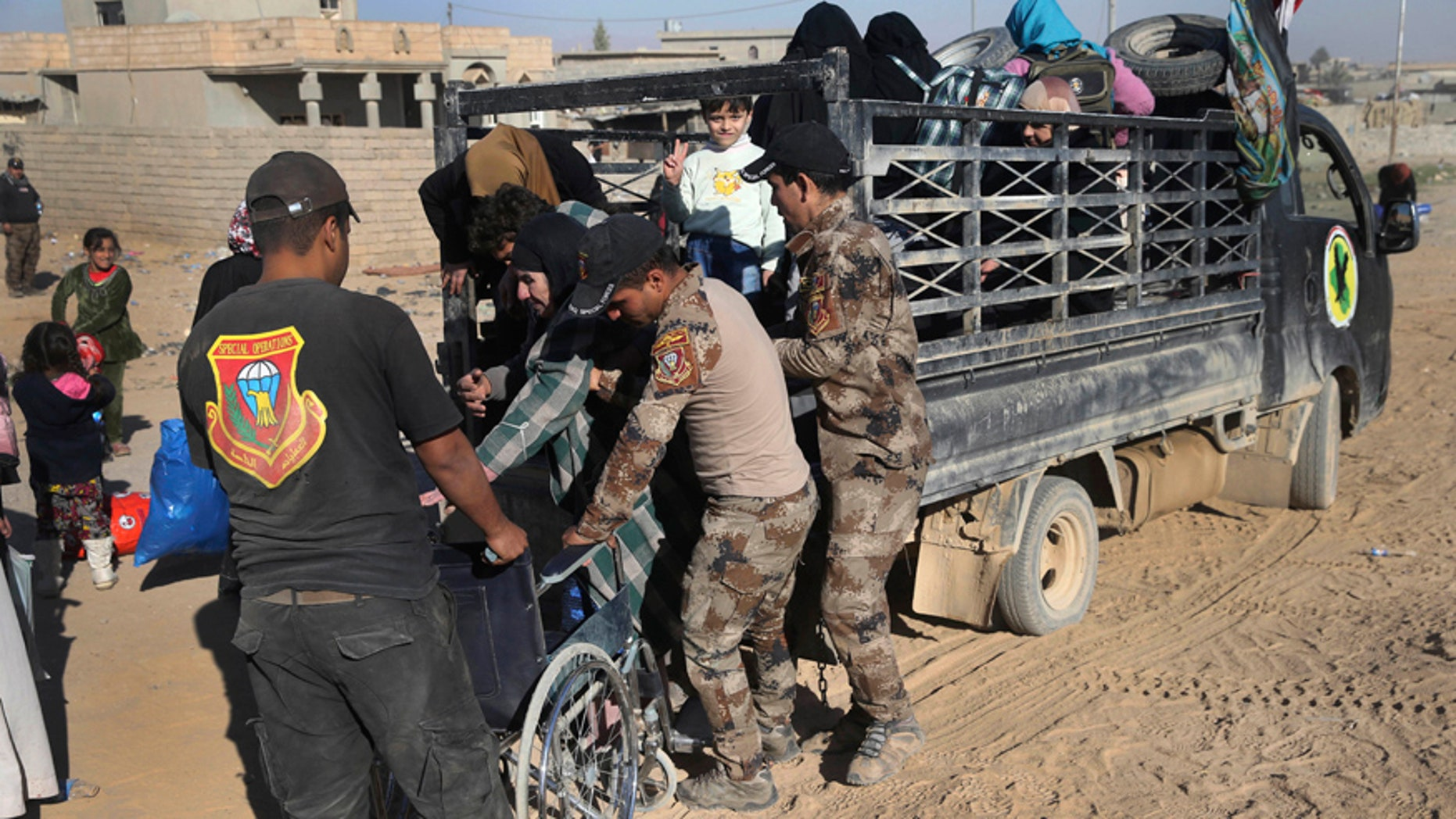 Nov. 23, 2016: Iraqi special forces soldiers help a handicapped woman, center, fleeing with her family the fighting between the Islamic State militants and Iraqi forces, in the Al-Samah neighborhood, in Mosul, Iraq.