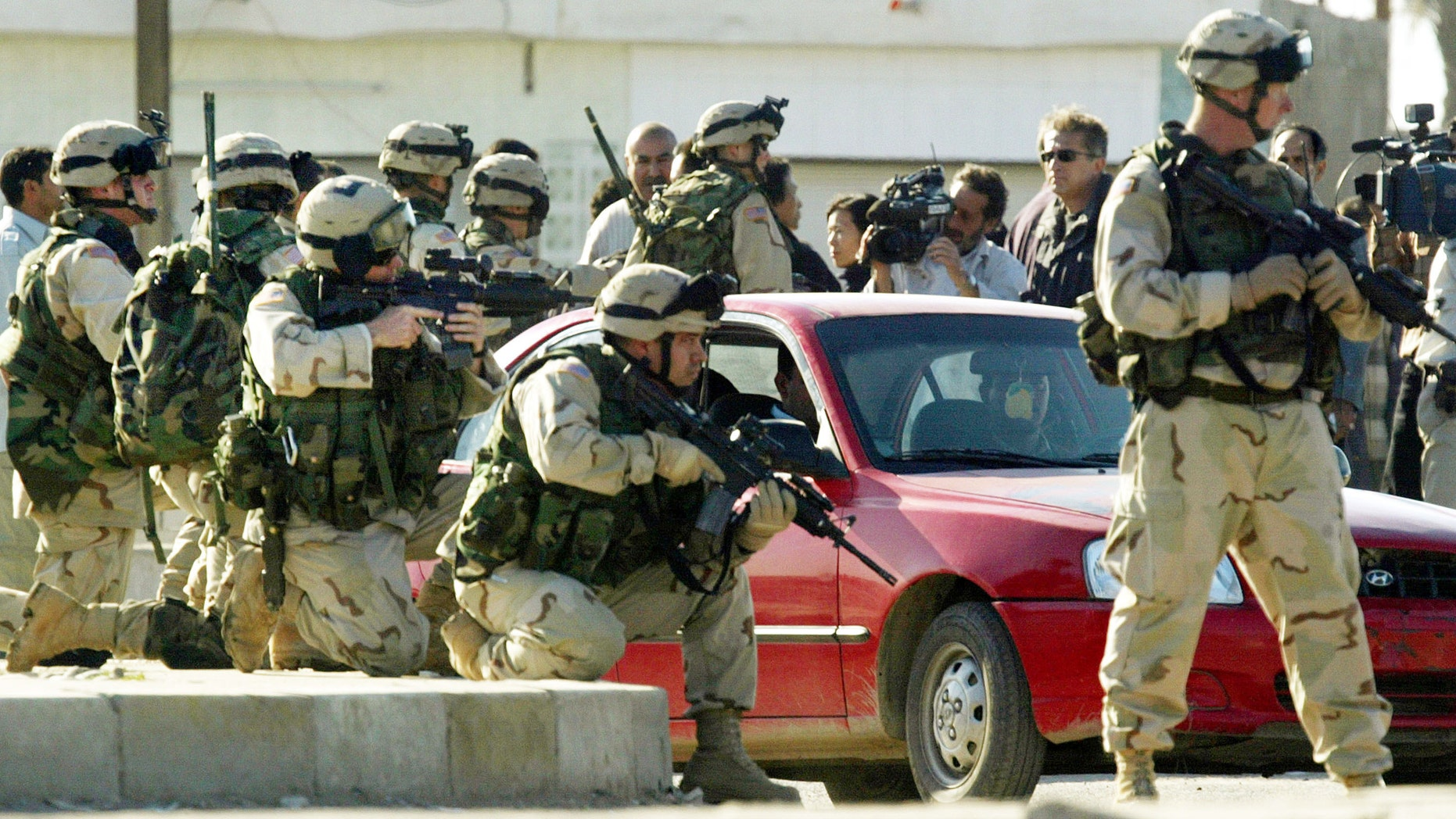 U.S. soldiers aim their rifles during a tense demonstration after a suicide car bomb exploded killing at least 50 people in Iraq.