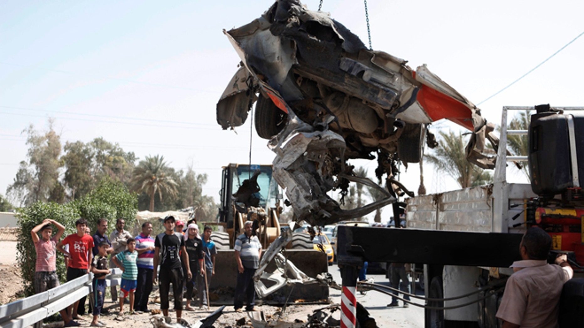 September 9, 2012: A destroyed car is moved from the scene of a car bomb attack in the town of Taji, about 12 miles north of Baghdad, Iraq.