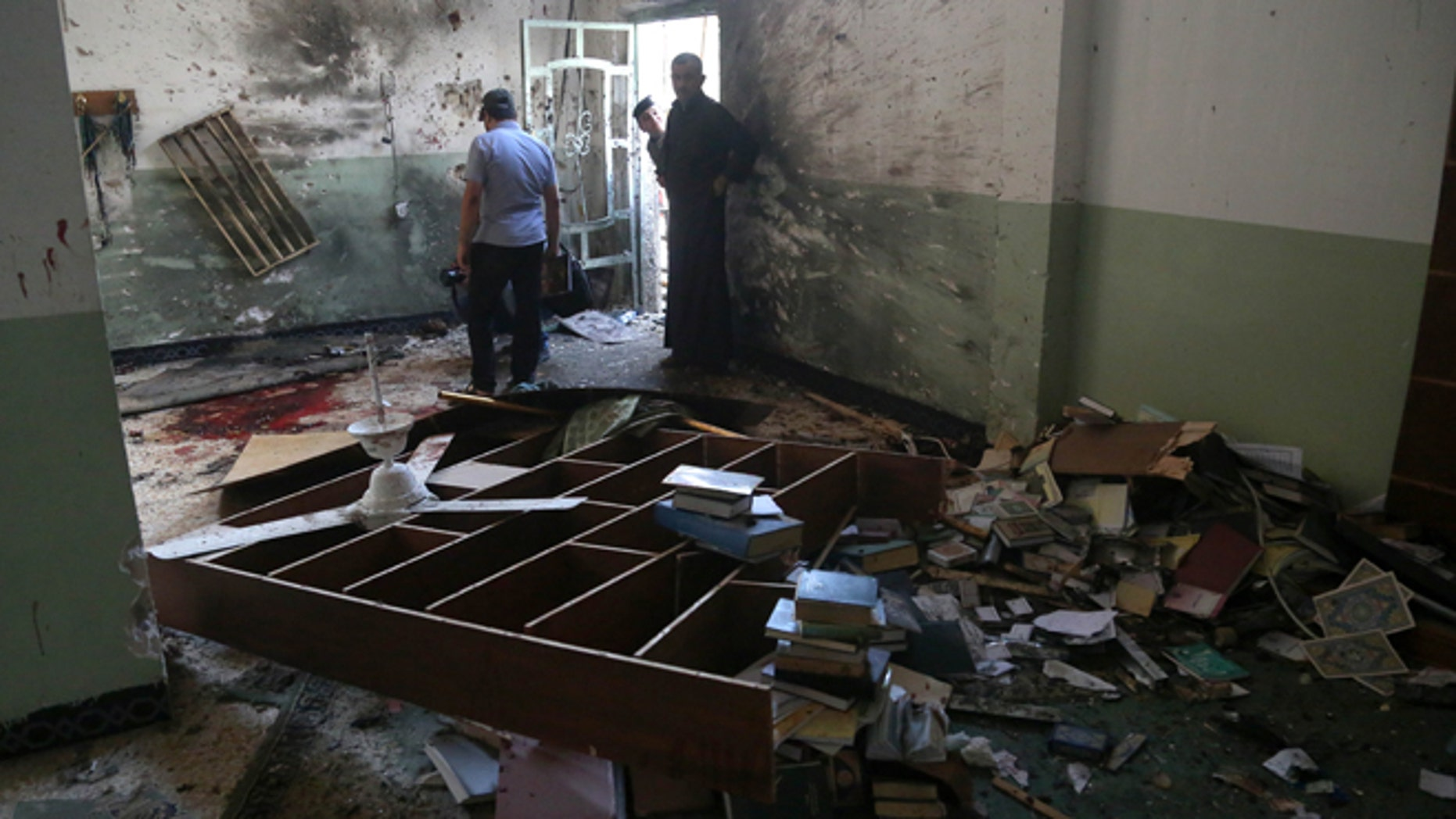 Aug. 25, 2014: Iraqis inspect the damage from an attack on the Imam Ali mosque in New Baghdad, Iraq. (AP/Khalid Mohammed)