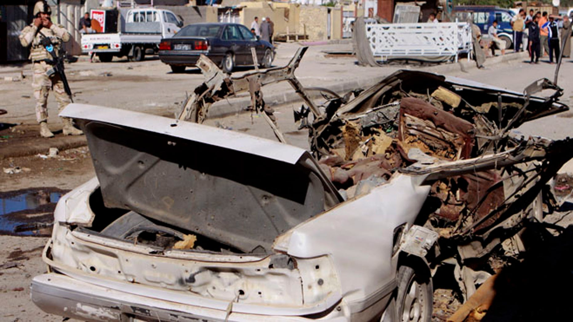 March 19, 2013: A federal policeman stands guard at the scene of a car bomb attack in the Shiite stronghold of Sadr City, Baghdad, Iraq. Insurgents unleashed deadly attacks Tuesday against Shiite areas in Baghdad, killing and wounding scores of people, police said.